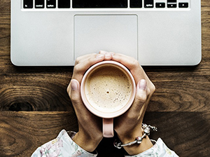 hands holding a hot drink above a laptop